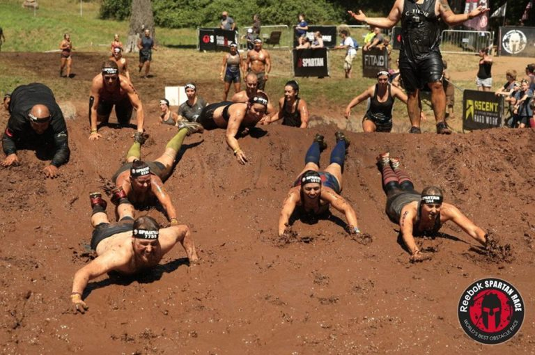 Those who cross a Spartan Sprint finish line together swimming through mud stay together! (Photo Credit: Spartan)